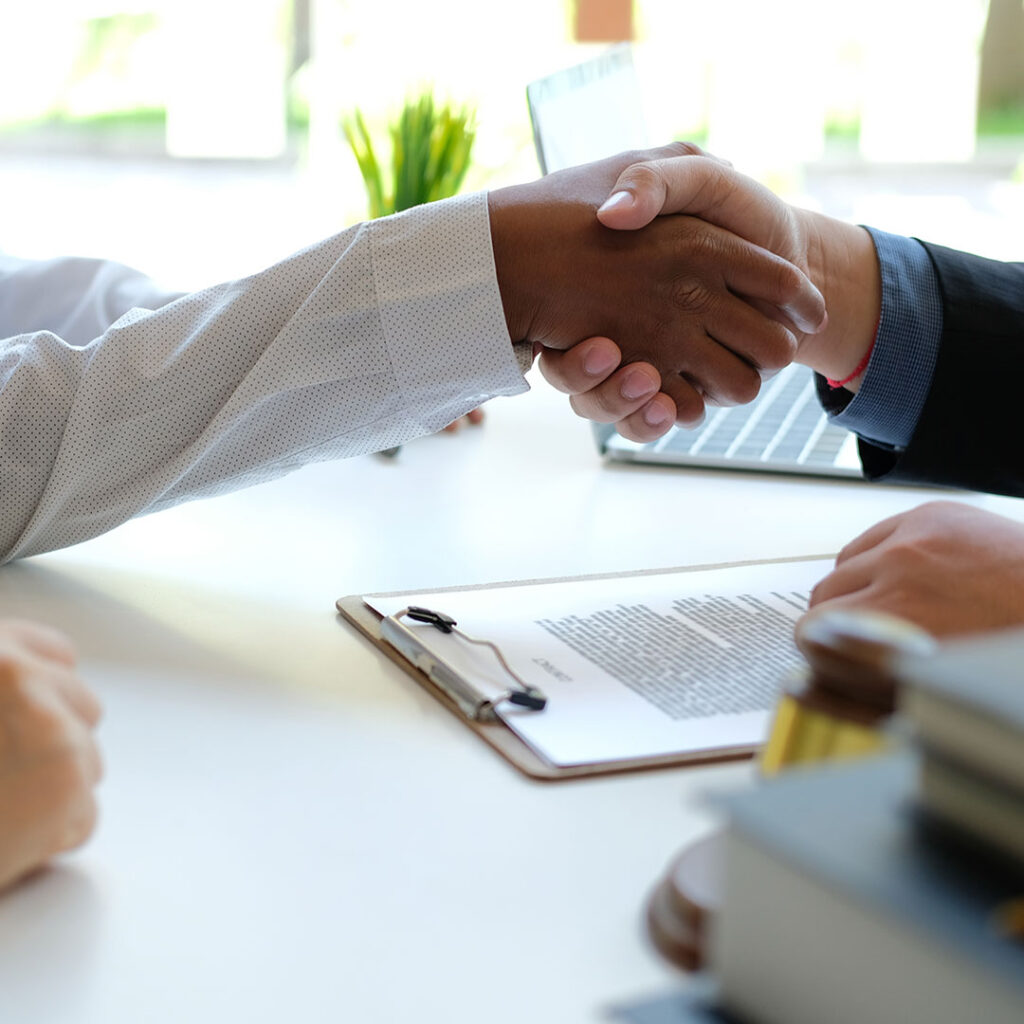 Real estate agent shaking hands with a client after they have signed paperwork.