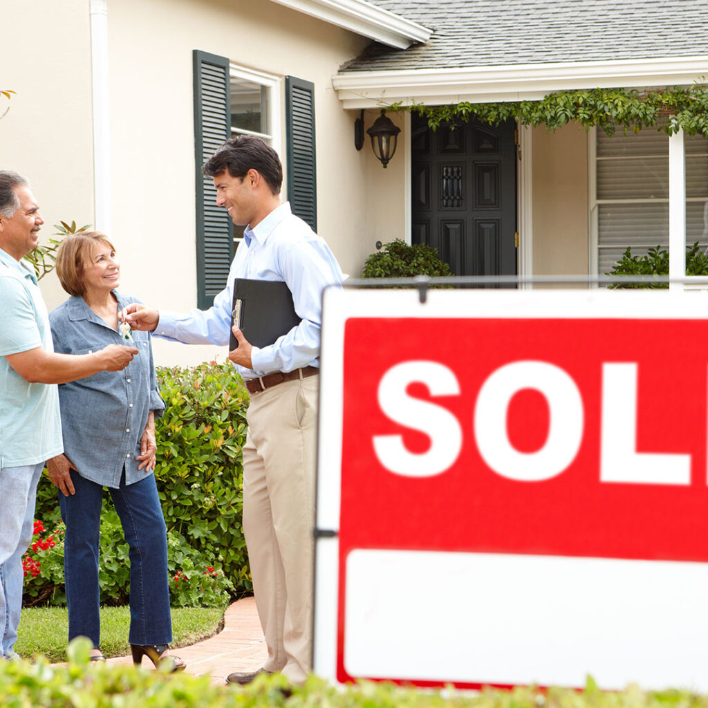 """A real estate agent handing the keys of the new home to the clients in front of a """"sold"""" sign."""