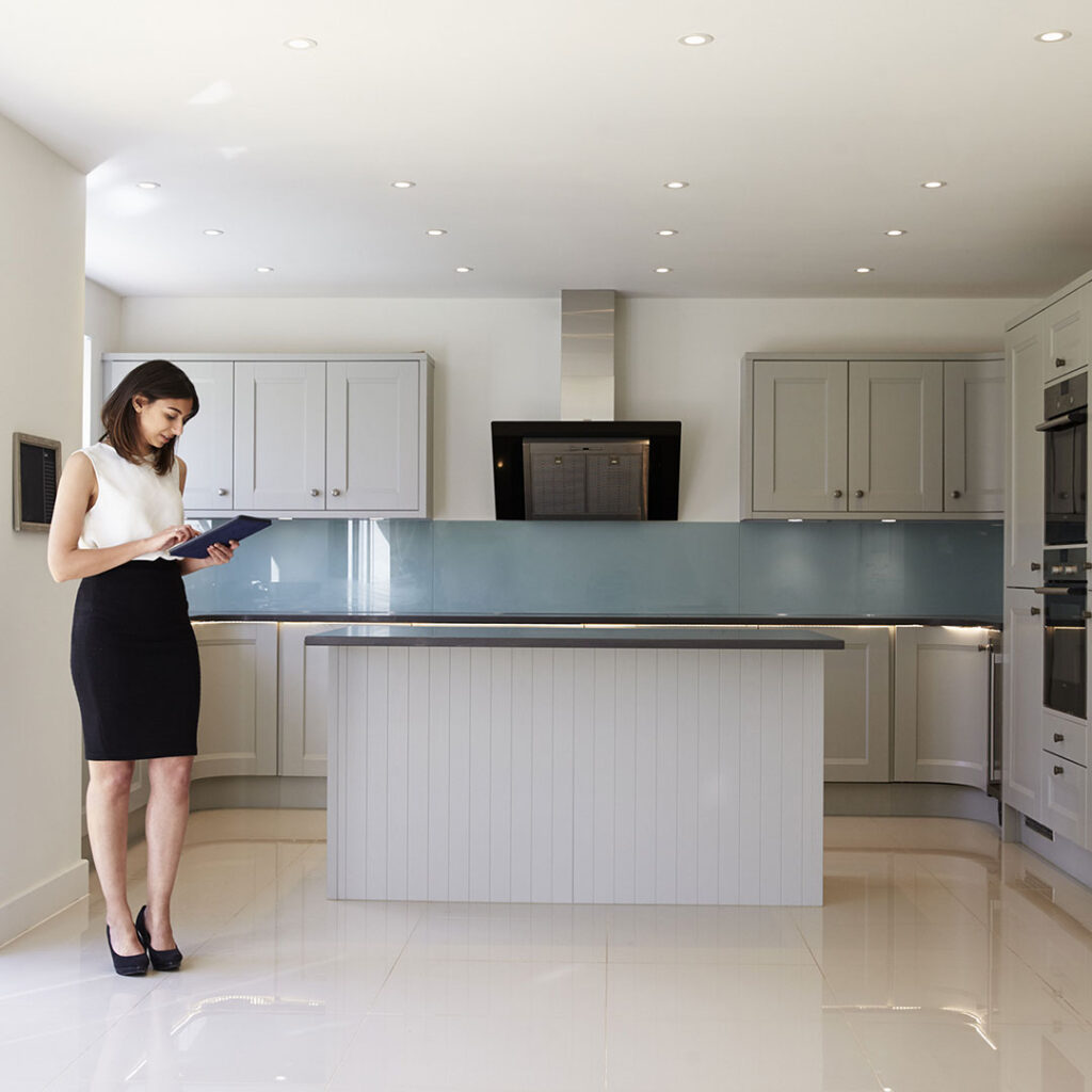 A real estate agent looking at a checklist on a clipboard while standing in a newly built home.