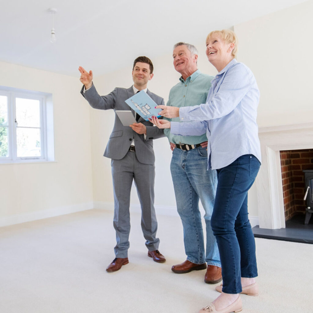 An older couple standing in a living room with a realtor.
