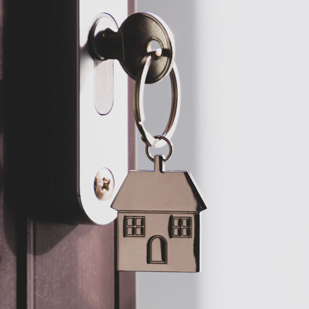 A house key stuck in a door lock with a house-shaped keychain hanging off of it.